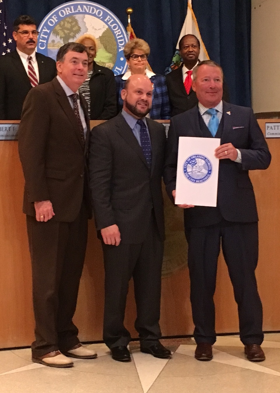 Orlando Commissioner Robert Stuart, left; UWWM Mediator/Arbitrator Lawrence Kolin, center; and Mayor Buddy Dyer pose for a picture after the City Council meeting.